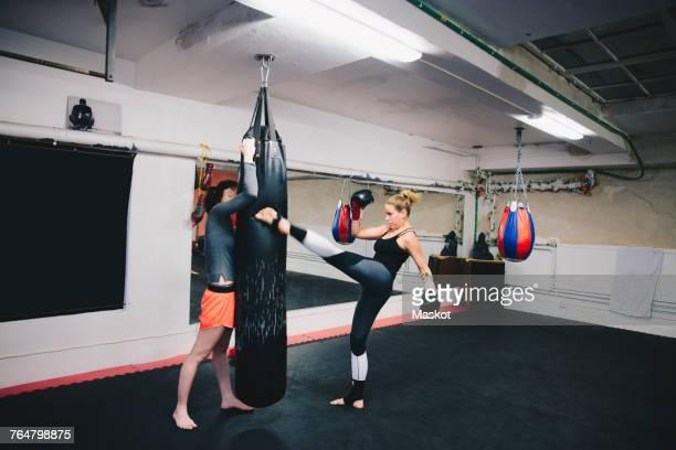 Female athletes practicing kickboxing at gym
