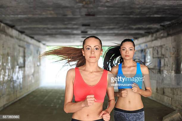 Female athletes running in underpass