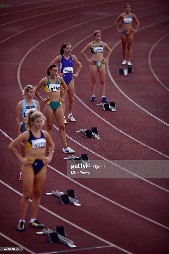 Female athletes standing behind starting blocks on track, elevated : Stock Photo
