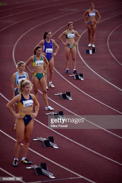 female athletes standing behind starting blocks on track, elevated - womens track stock photos and pictures