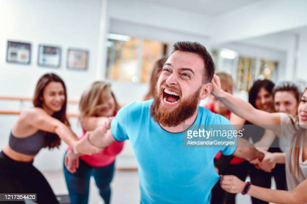 female athletes tormenting their male colleague in gym - female torture stock pictures, royalty-free photos & images
