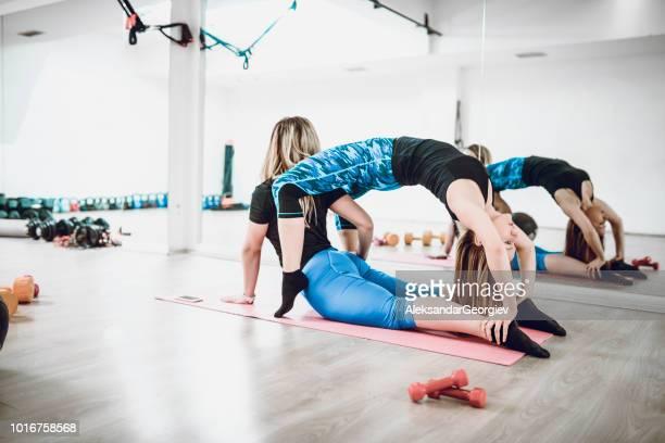 Female Athletes Working On Flexibility And Balance Together