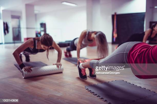 Female Athletes Working Out Together During Fitness Class In Gym