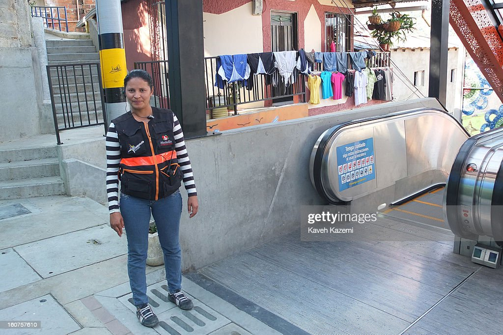 A female attendant equipped with two way radio stands by the escalators in '20 de Julio' neighborhood in the Comuna 13 slums on January 5, 2013 in Medellin, Colombia. The stairway is divided into six sections and has a length of 1,260 feet. An escalator goes up and a second goes down.Residents used to climb hundreds of steps to get home from the bottom of the hill, but the journey now takes just 6 minutes. Comuna 13 is the most notorious slums of Medellin with violence occurring everyday.