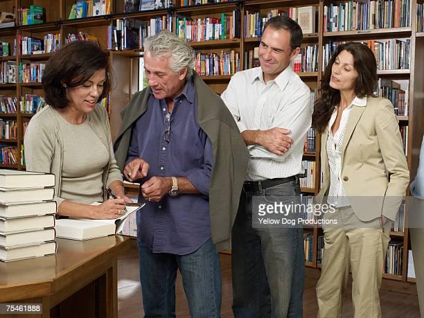 female author signing books for customers in bookstore - lançamento de livro evento publicitário - fotografias e filmes do acervo