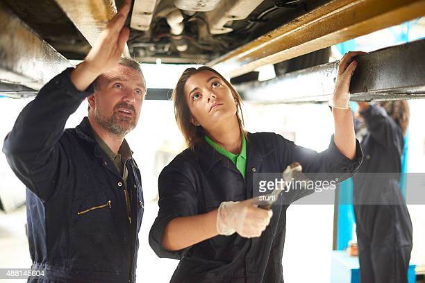 Female auto mechanic trainee  with her tutor
