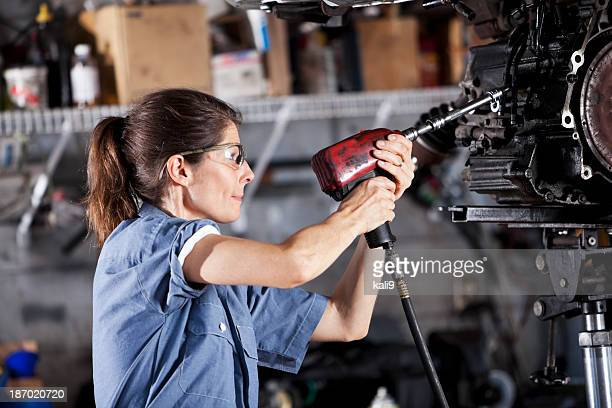 Female auto mechanic working on car transmission