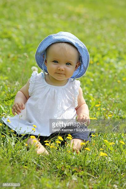 Female baby sitting in flower meadow in summer