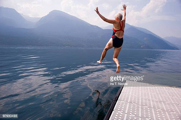 female babyboomer jumping into lake - actieve ouderen stockfoto's en -beelden