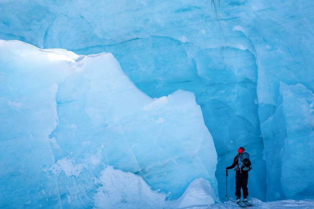 Female backcountry skier approaches glacier in mountain