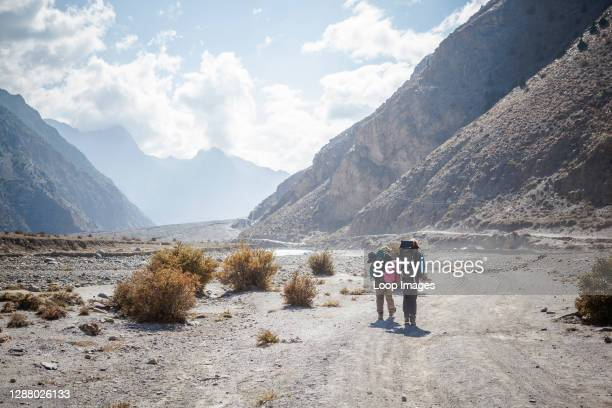 Female backpacker and sherpa hiking on the dusty trail towards the Kali Gandaki gorge.