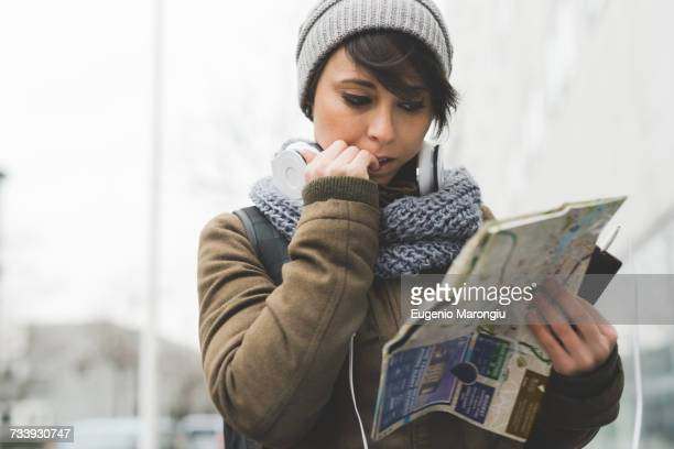 Female backpacker biting nails and looking at map in city