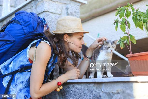 Female backpacker caressing a cat on street