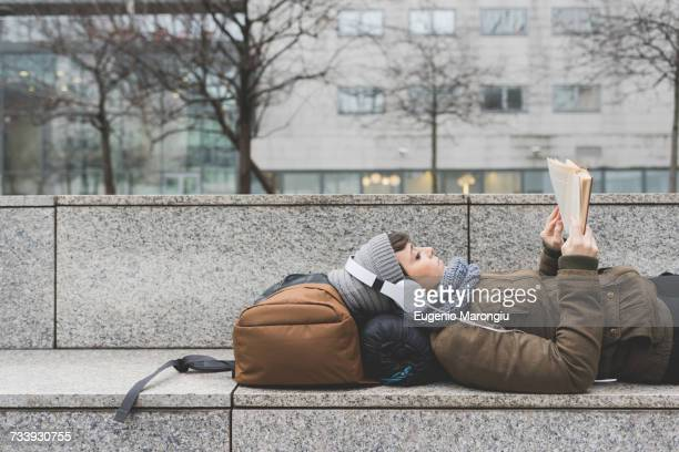 Female backpacker lying on back reading book on wall