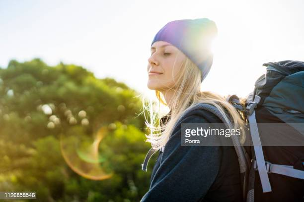 female backpacker meditating on sunny day - mid length hair stock pictures, royalty-free photos & images