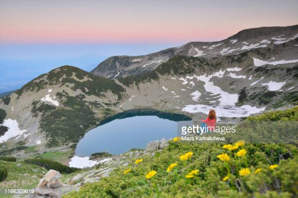 female backpacker sitting on a rock enjoying beautiful view of mountain lake with flowers in the foreground - pirin mountains stock pictures, royalty-free photos & images