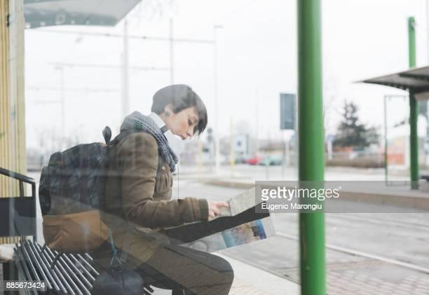 Female backpacker waiting at bus station looking at map