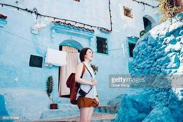 Female backpacker walking on a blue color street