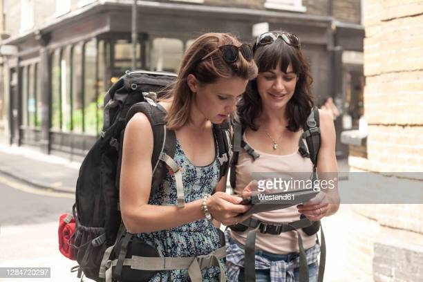 female backpackers using digital tablet for guidance map while exploring city - direction stock pictures, royalty-free photos & images