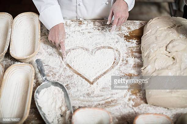 Female baker drawing heart in flour on a wooden table top