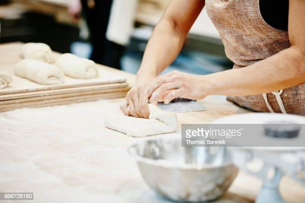 Female baker folding dough for baguettes in bakery