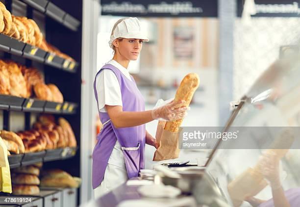 Female baker packing loaf of bread in bakery.