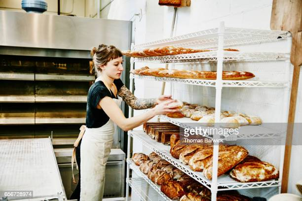 Female baker placing bread fresh from oven on cooling rack