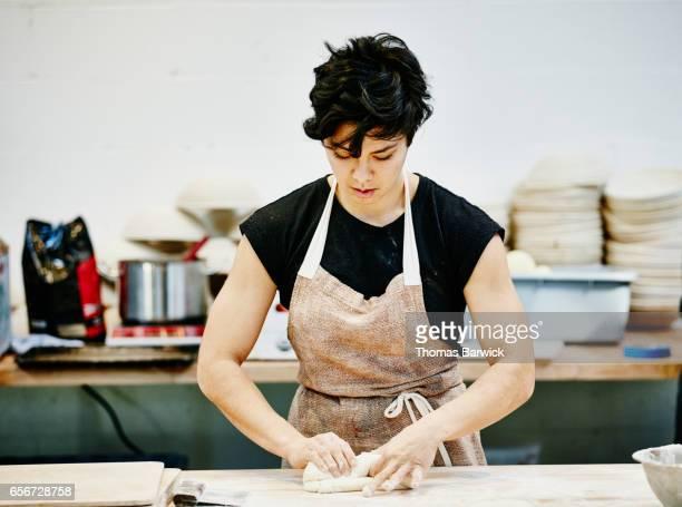 Female baker shaping dough in commercial bakery