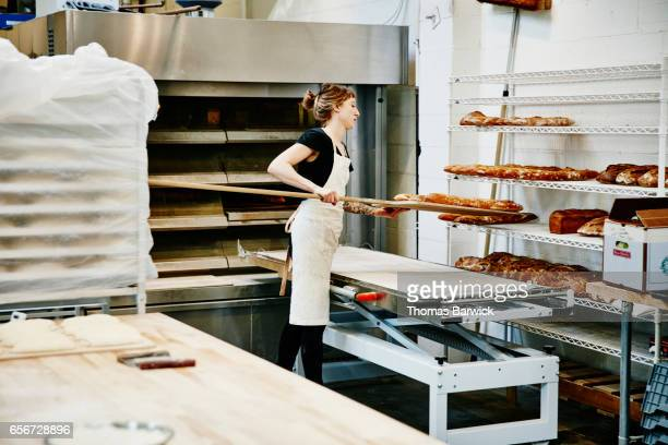 Female baker using peel to move baguettes from oven to cooling rack