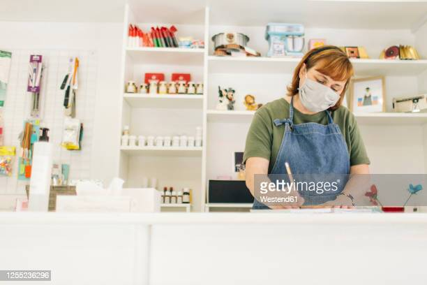 female baker wearing mask writing in book on checkout counter at shop - small business stock pictures, royalty-free photos & images