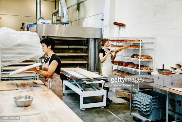Female bakers preparing bread in bakery