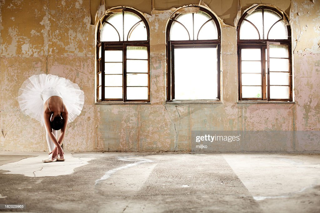 A female ballerina posing by a set of windows : Stock Photo