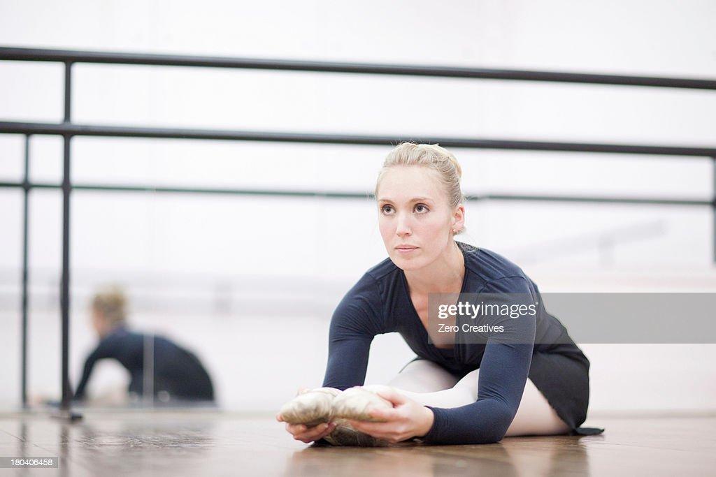 Female ballerina stretching on the floor : Stock-Foto