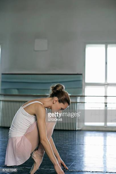 A female ballet dancer crouching on the toe-cap
