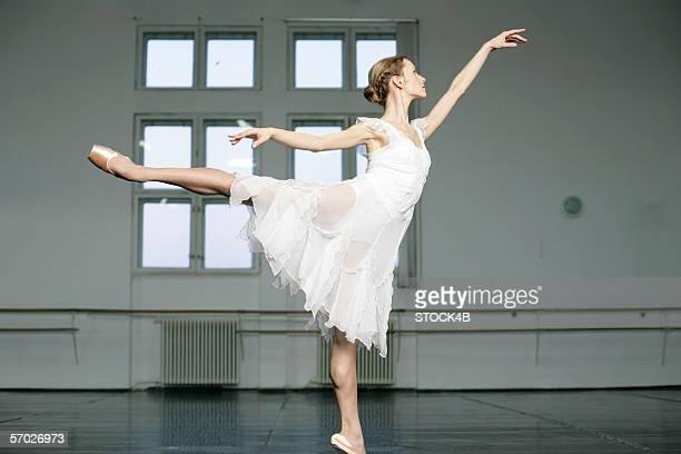 a female ballet dancer doing an arabesque - アラベスクポジション ストックフォトと画像