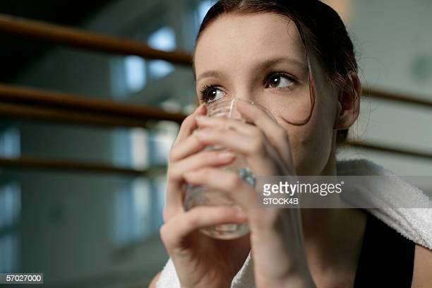 A female ballet dancer drinking a glass of water