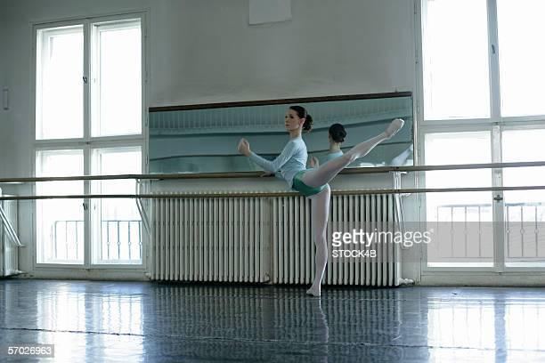 A female ballet dancer exercising an attitude at ballet bare