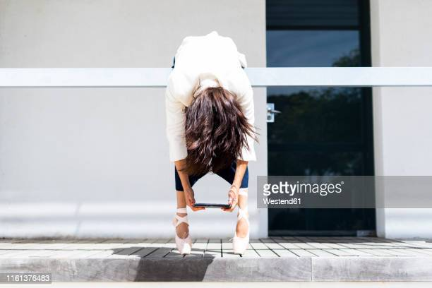 female ballet dancer hanging over railing, holding tablet - flaccid stock photos and pictures
