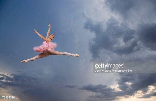 Female ballet dancer in mid air in sky