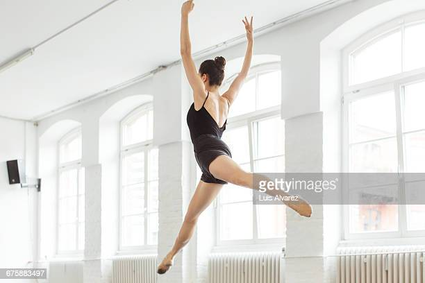 female ballet dancer jumping in mid-air at studio - rodete fotografías e imágenes de stock