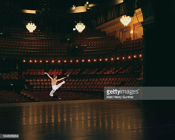 female ballet dancer jumping onstage - teatro foto e immagini stock