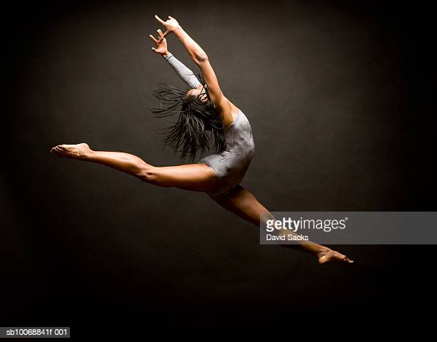 female ballet dancer leaping in air - ballet dancer stock pictures, royalty-free photos & images
