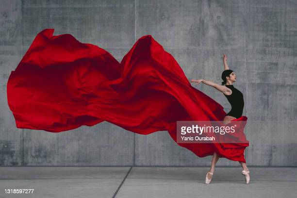 female ballet dancer on pointes dancing with a red veil in front of a grey concrete wall - dance troupe bildbanksfoton och bilder