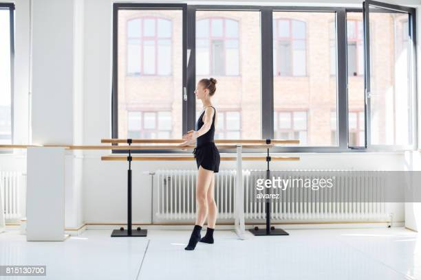 Female ballet dancer performing at barre in studio