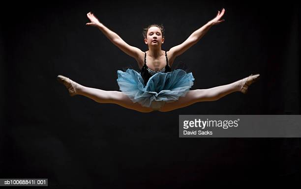 Female ballet dancer performing splits in air
