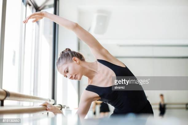 Female ballet dancer practicing at barre in studio