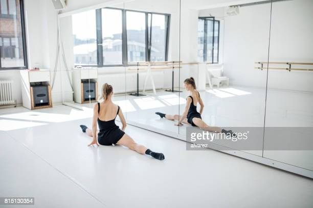 female ballet dancer practicing splits by mirror - rehearsal stock pictures, royalty-free photos & images