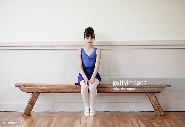Female ballet dancer sitting on bench at practise