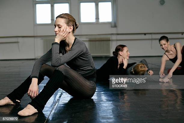 A female ballet dancer sitting separated of a group