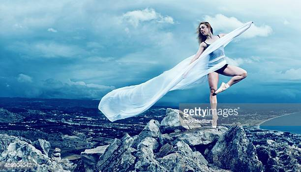 Female ballet dancer stands on her toes on a mountain